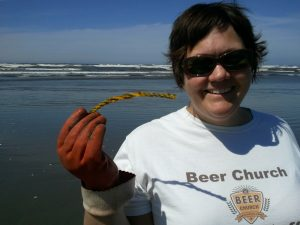 "Kim holds up an example of one of the 10,000 little bits of yellow rope we will probably find on the beach again this year. Courtesy of the local ""aquaculture"" ratbastard litterbug seafood farmers."