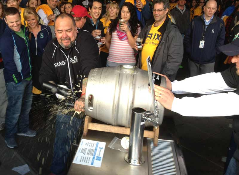 Mike Armstrong tapping a  firkin of beer at Safeco Field.
